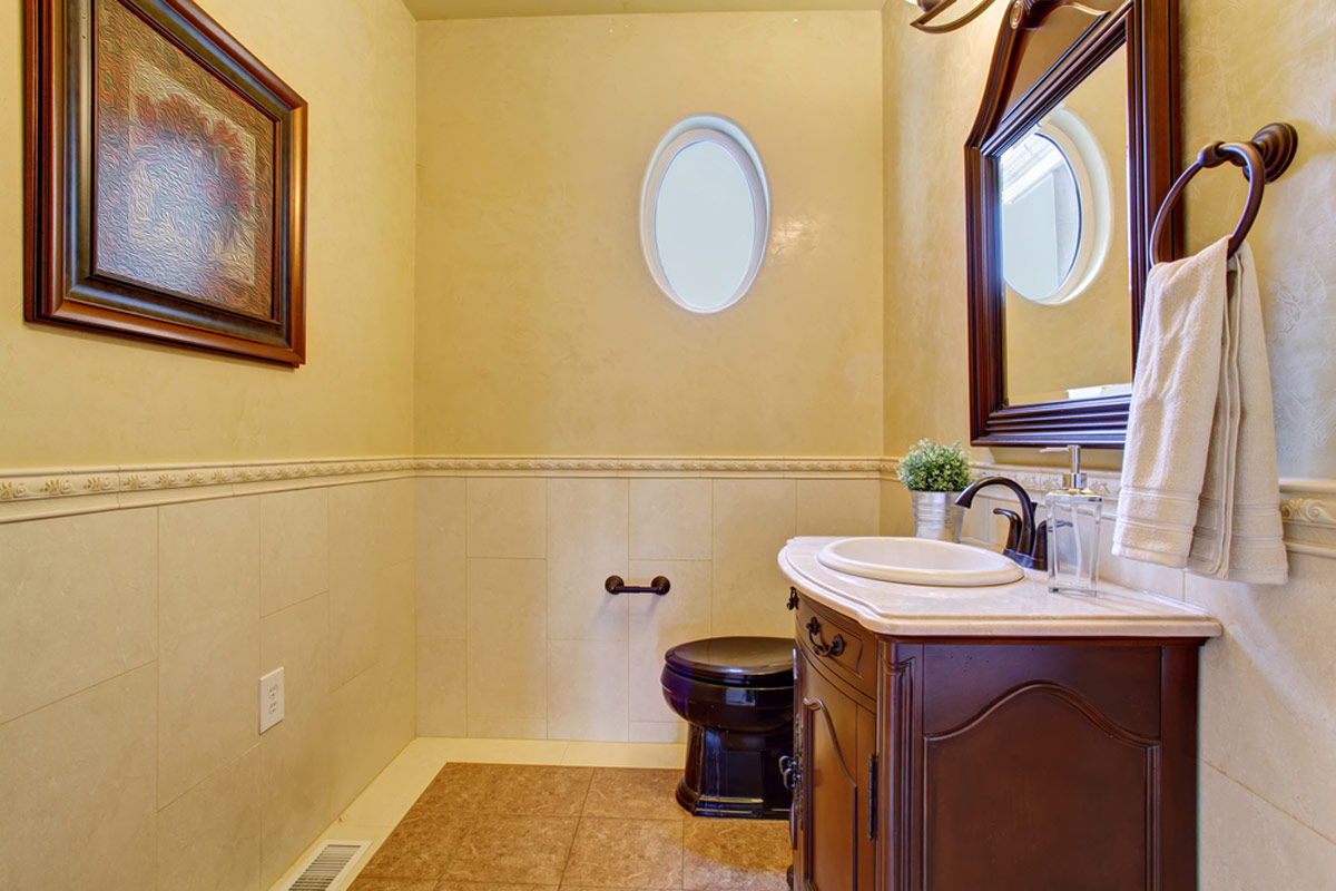 Classy Half Bathroom Addition With Small Oval Window and Beige Tile Floor