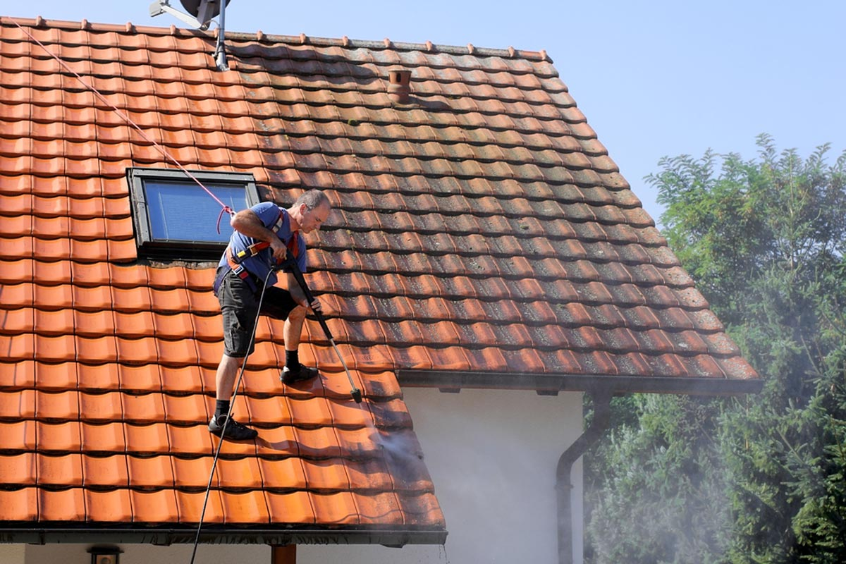 Contractor Washing A Roof With Steep Pitch