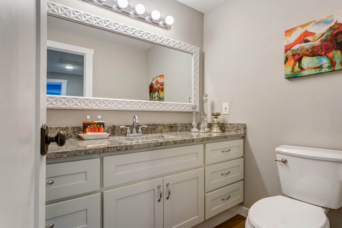 Newly Added Bathroom With A White Vanity Cabinet And Grey Counter Top