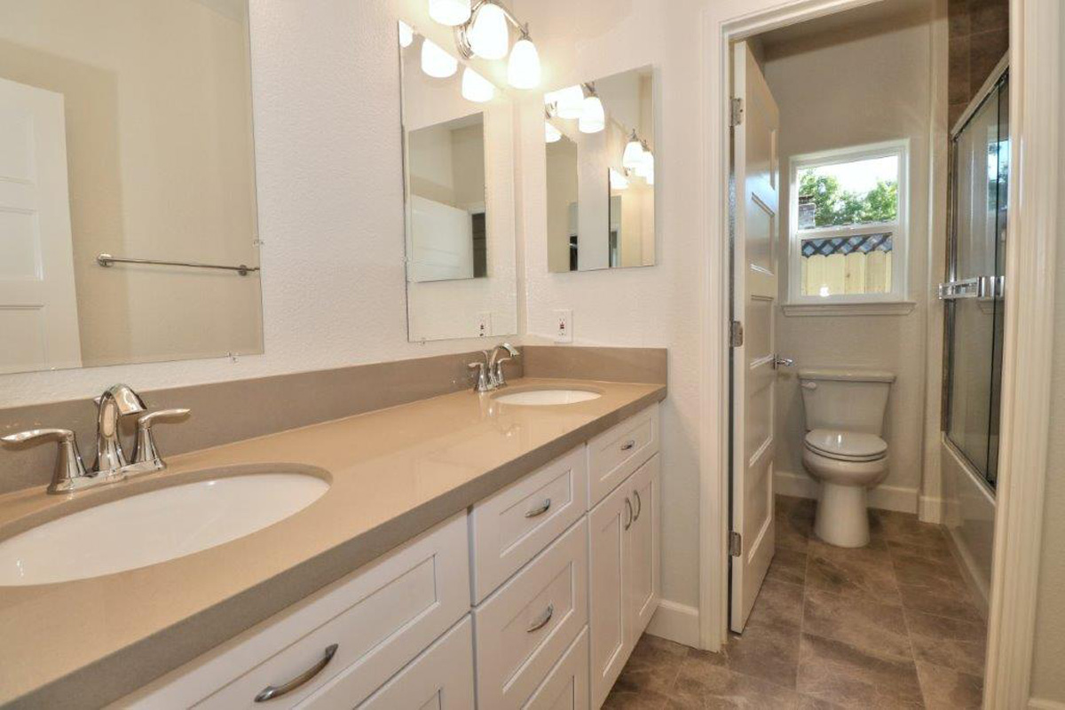 Typical Bathroom Renovation - Classic double sink, white cabinets, tile flooring